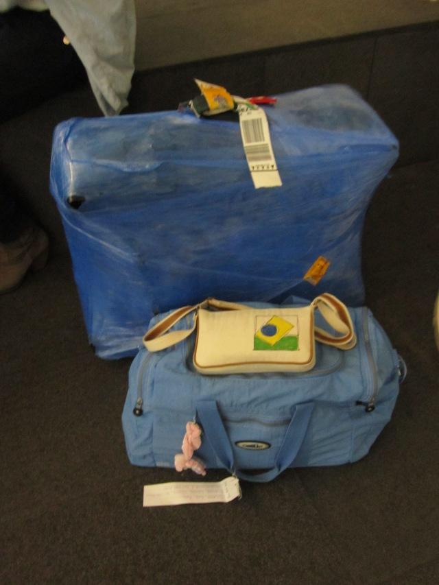 Minha mala destruída, logo após ser embalada com plástico azul